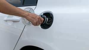 A person removes a fuel cap for emission testing