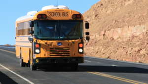 School Bus driving down an Arizona road