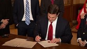 Governor Doug Ducey signing a document