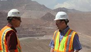To mine employees wearing hard hats and safety vests having a discussion in front of a pit mine